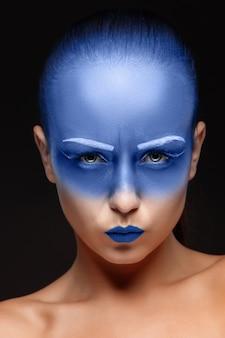 Retrato de uma mulher que posa coberta com tinta azul