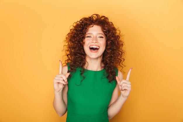 Retrato de uma mulher ruiva cacheada sorridente apontando
