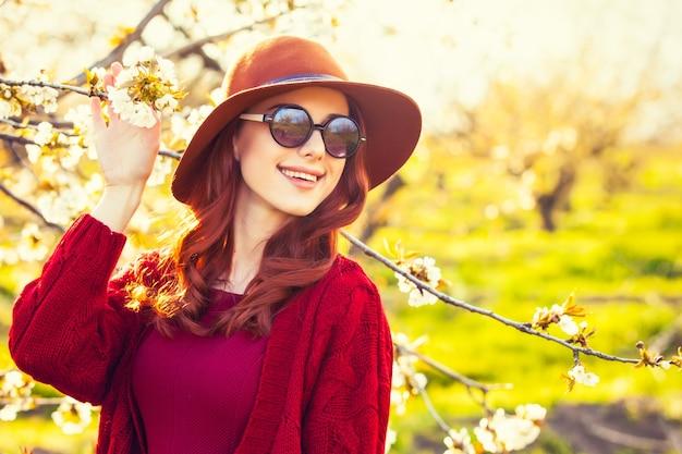 Retrato de uma mulher ruiva linda de suéter vermelho e chapéu no jardim flor macieira na primavera no pôr do sol.
