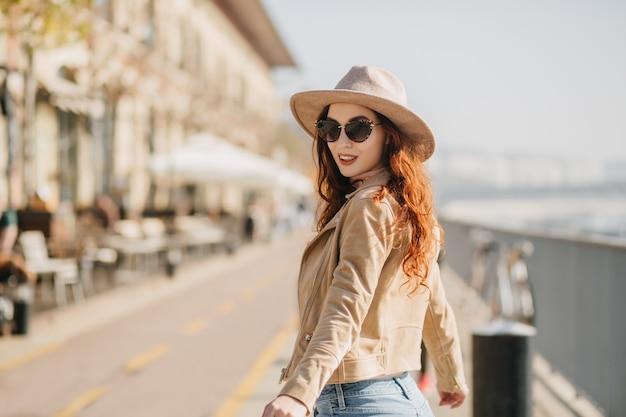 Retrato de uma mulher ruiva rindo, olhando por cima do ombro enquanto caminhava pela rua