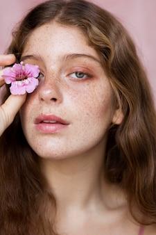 Retrato de uma mulher sardenta cobrindo o olho com uma flor
