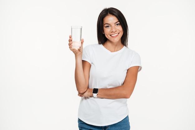Retrato de uma mulher saudável sorridente segurando copo com água