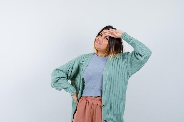 Retrato de uma mulher segurando a cabeça em roupas casuais e com uma vista frontal alegre