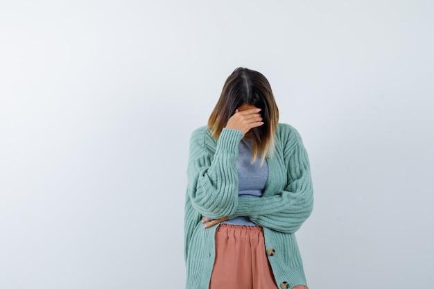 Retrato de uma mulher segurando a mão sobre a cabeça, curvada em roupas casuais e com uma vista frontal deprimida