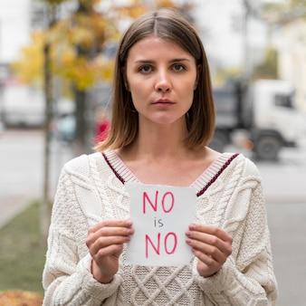 Retrato de uma mulher segurando um cartaz de alerta