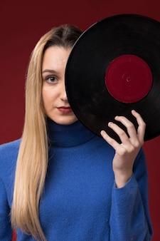 Retrato de uma mulher segurando um disco de vinil