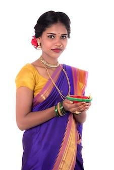 Retrato de uma mulher segurando uma foto de diya, diwali ou deepavali com mãos femininas segurando uma lâmpada a óleo durante o festival de luz sobre fundo branco