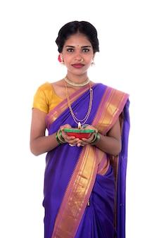 Retrato de uma mulher segurando uma foto de diya, diwali ou deepavali com mãos femininas segurando uma lamparina durante o festival de luz na parede branca