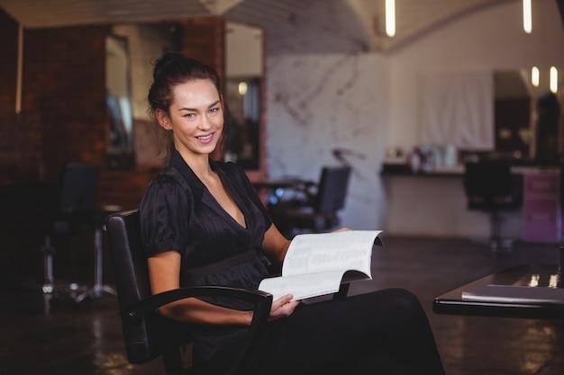 Retrato de uma mulher segurando uma revista no salão de cabeleireiro
