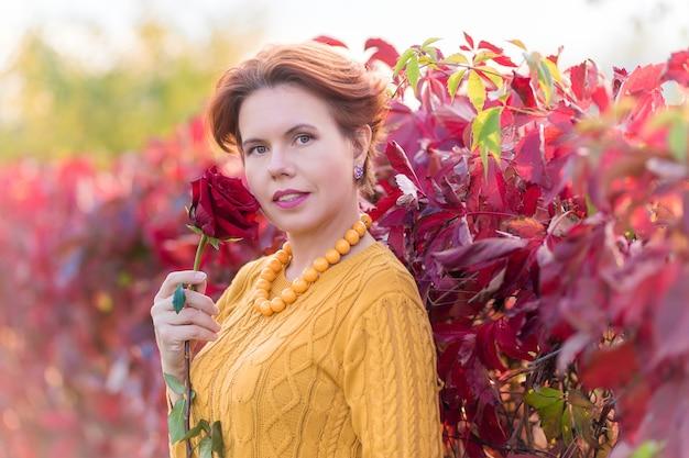 Retrato de uma mulher segurando uma rosa e em pé perto do arbusto de folhas de videira selvagem vermelha no parque outono olhando
