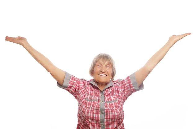 Retrato de uma mulher sênior alegre gesticulando vitória sobre um fundo branco