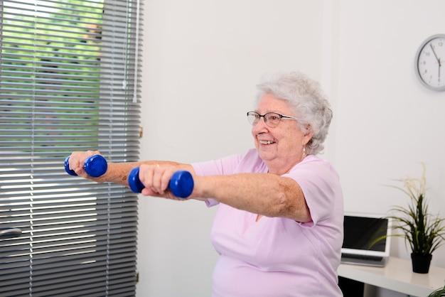 Retrato de uma mulher sênior ativa e dinâmica fazendo esporte fitness em casa