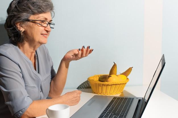 Retrato de uma mulher sênior usando laptop. mulher idosa falando por link de vídeo. conceito de videochamada, novo normal, auto-isolamento
