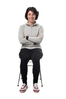 Retrato de uma mulher sentada em uma cadeira em fundo branco, braços cruzados