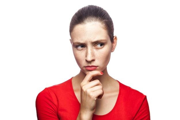 Retrato de uma mulher séria e pensativa em uma camiseta vermelha com sardas