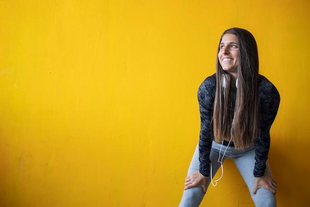 Retrato de uma mulher sexy de construção muscular de pé contra uma parede amarela