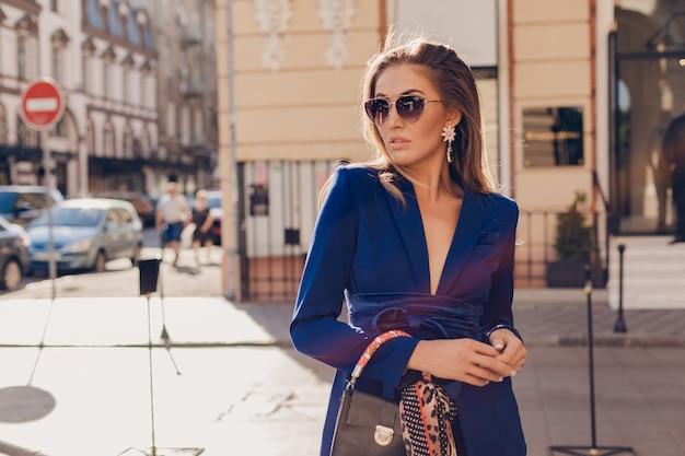Retrato de uma mulher sexy e elegante andando na rua com um terno azul e óculos de sol em um dia ensolarado de verão