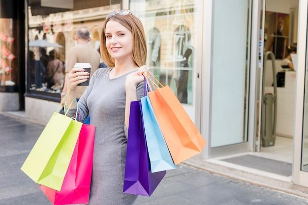 Retrato de uma mulher shopaholic com sacolas coloridas