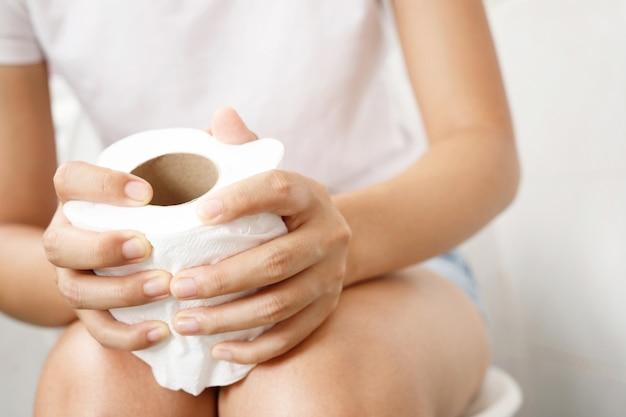 Retrato de uma mulher sofre de diarréia e dor de estômago. dor e problema. mão segure o rolo de papel de seda na frente do vaso sanitário. prisão de ventre no banheiro. higiene, conceito de saúde.