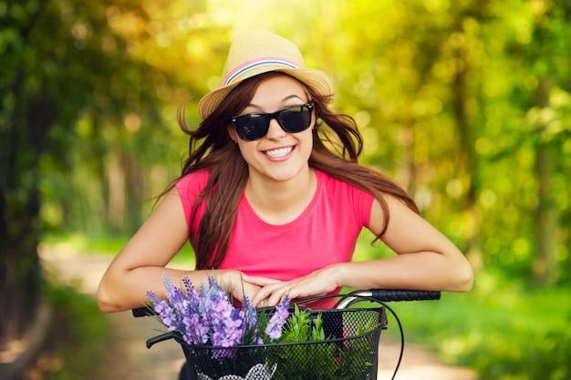 Retrato de uma mulher sorridente andando de bicicleta no parque