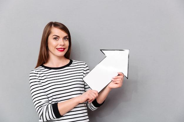 Retrato de uma mulher sorridente apontando a seta de papel para cima