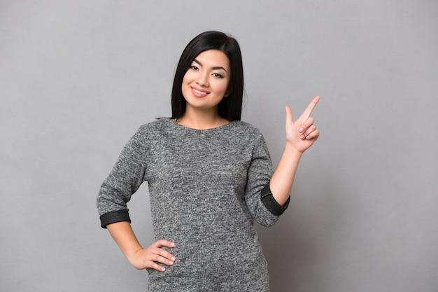 Retrato de uma mulher sorridente apontando o dedo na copyspace sobre uma parede cinza e olhando para a frente