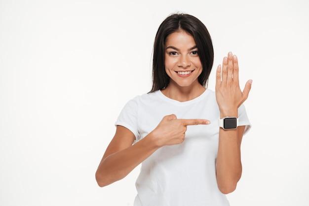 Retrato de uma mulher sorridente, apontando o dedo no relógio inteligente