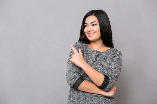 Retrato de uma mulher sorridente apontando o dedo para uma parede cinza