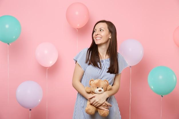 Retrato de uma mulher sorridente atraente no vestido azul olhando de lado segurando e abraçando o ursinho de pelúcia brinquedo no fundo rosa com balões de ar coloridos. emoções sinceras de pessoas de festa de férias de aniversário.