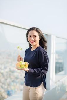 Retrato de uma mulher sorridente caucasiana atraente comendo salada em um dia ensolarado de verão, sentado na grama verde no parque, foco no garfo com salada