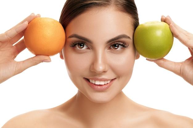 Retrato de uma mulher sorridente caucasiana atraente isolada no branco segurando uma maçã verde e uma laranja