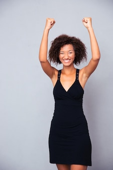 Retrato de uma mulher sorridente celebrando seu sucesso na parede cinza