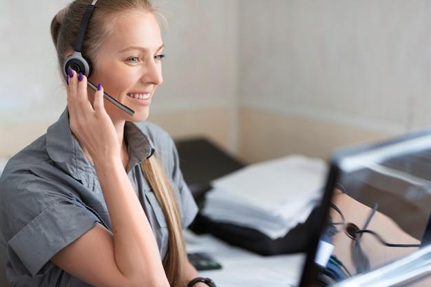 Retrato de uma mulher sorridente com fone de ouvido trabalhando em um call center.