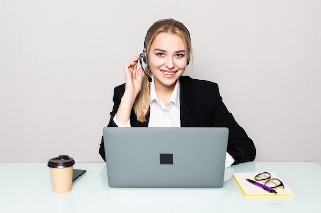 Retrato de uma mulher sorridente com o operador de linha de laptop portátil com fones de ouvido no escritório