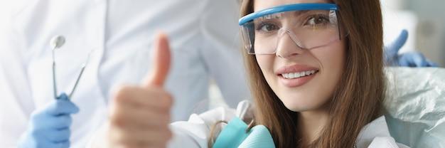 Retrato de uma mulher sorridente com o polegar levantado durante uma consulta no dentista