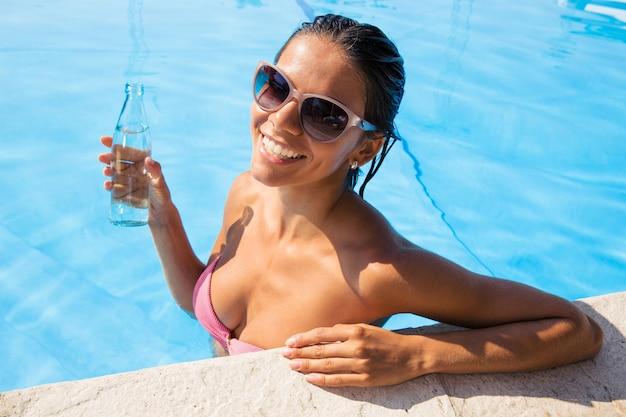 Retrato de uma mulher sorridente com óculos de sol em pé na piscina e segurando uma garrafa com água ao ar livre