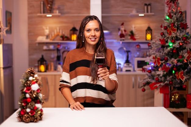 Retrato de uma mulher sorridente com uma taça de vinho na mão