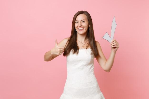 Retrato de uma mulher sorridente com vestido branco, mostrando o polegar para cima e segurando a marca de seleção