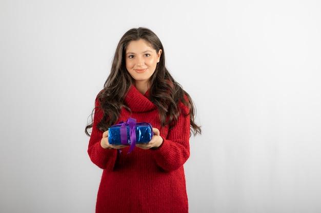 Retrato de uma mulher sorridente, dando uma caixa de presente de natal com fita roxa.