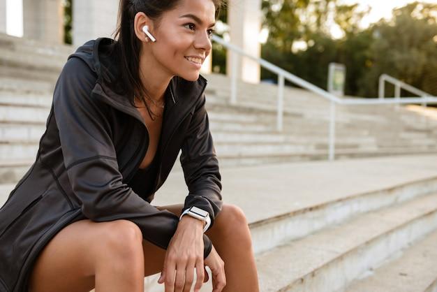 Retrato de uma mulher sorridente de aptidão em fones de ouvido