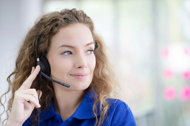 Retrato de uma mulher sorridente de camisa azul, trabalhando com fone de ouvido.