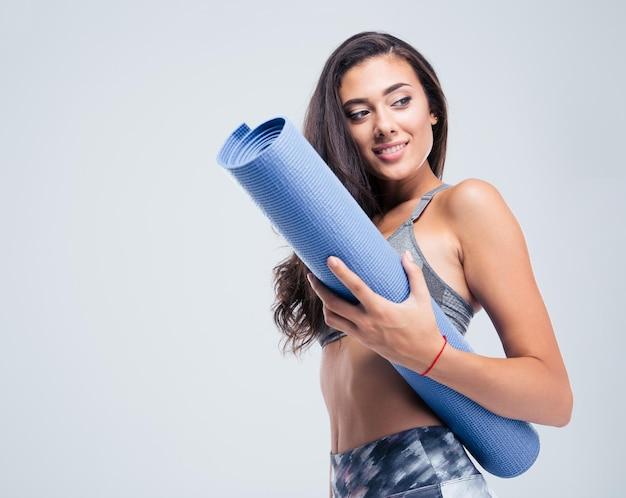 Retrato de uma mulher sorridente de esportes segurando um tapete de ioga isolado em uma parede branca