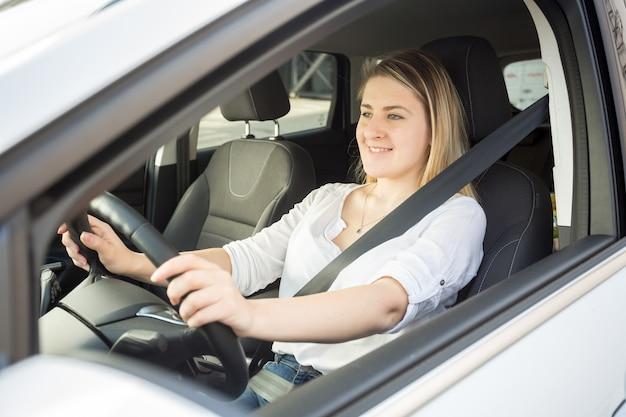 Retrato de uma mulher sorridente, dirigindo um carro e olhando para a câmera