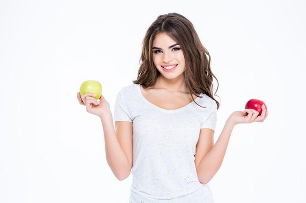 Retrato de uma mulher sorridente e adorável segurando duas maçãs isoladas em uma parede branca