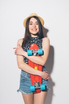 Retrato de uma mulher sorridente e animada furando o skate isolado na parede branca