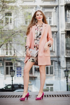 Retrato de uma mulher sorridente e atraente caminhando pelas ruas da cidade com casaco rosa e vestido floral
