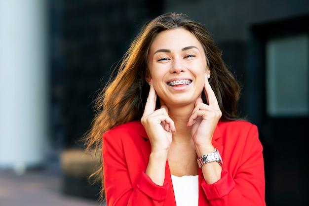 Retrato de uma mulher sorridente e feliz rindo no aparelho, fora ou ao ar livre
