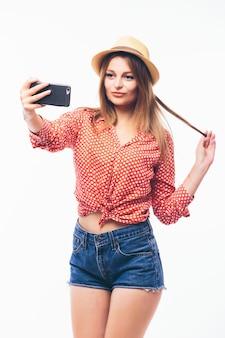 Retrato de uma mulher sorridente e fofa fazendo selfie em um smartphone isolado em um fundo branco