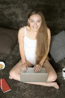 Retrato de uma mulher sorridente em cueca sentado com laptop