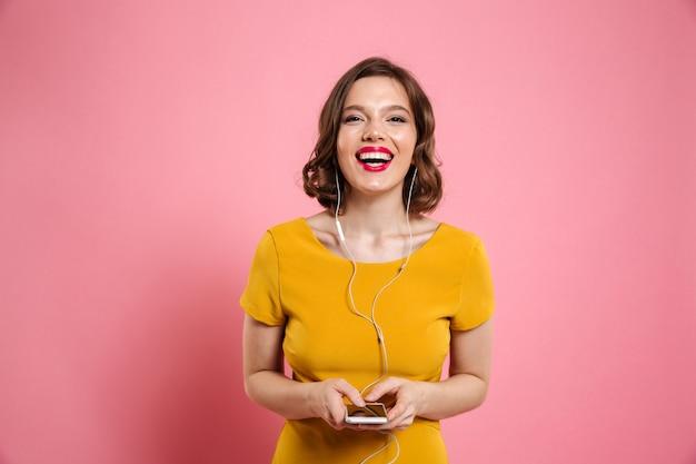 Retrato de uma mulher sorridente em fones de ouvido, ouvindo música
